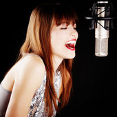 Girl singing to the microphone in a studio — Stockfoto