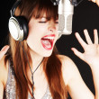 Royalty-Free Stock Photo: Girl singing to the microphone in a studio