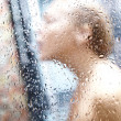 Royalty-Free Stock Photo: Shower drops blurred close up photo of young woman taking shower. Focused o