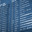 Stock Photo: Close up view of airport time-table blue toned