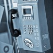 Close up view of public phone on blue back - Stock Photo