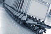 Close up view of trolleys luggage in a raw in airport — Stock Photo