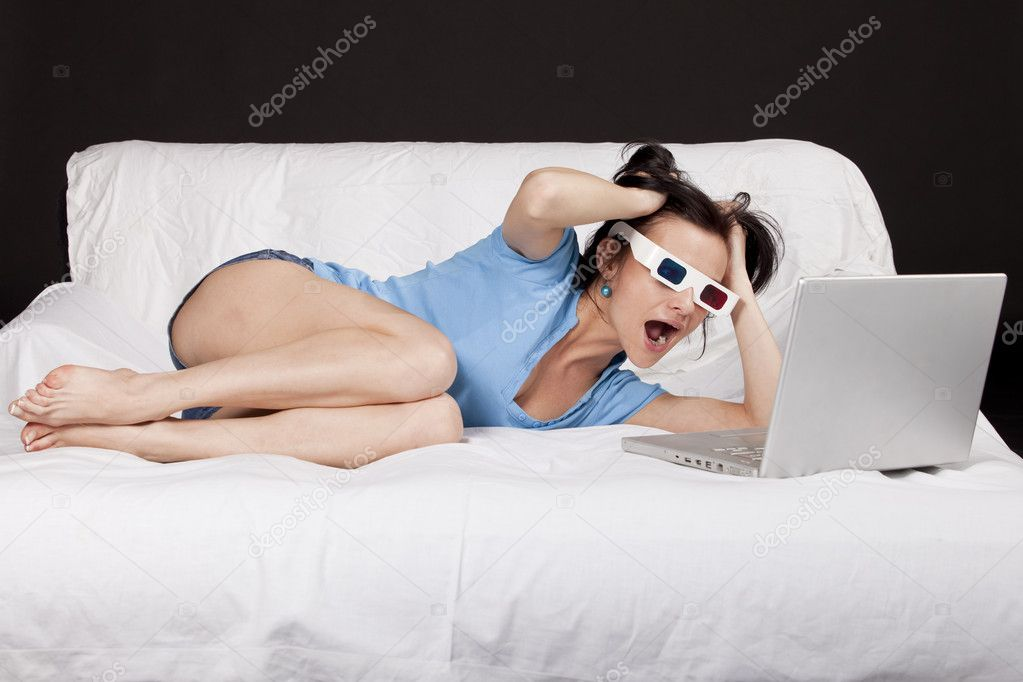 Young  woman with plastic 3d colored glasses pulling her hair and watching a 3d movie on bed, on a laptop. Part of photo series. Studio shot  Stock Photo #4213317