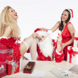 Santa Claus with two sexy helpers in his office — Stockfoto