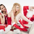 Santa Claus with two sexy helpers in his office — Stock Photo #4500216