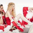 SantClaus with two sexy helpers in his office — Stockfoto #4500217