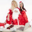 Stock Photo: Santa Claus with two sexy helpers in his office