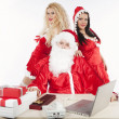 Santa Claus with two sexy helpers in his office — Lizenzfreies Foto