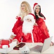 Santa Claus with two sexy helpers in his office — Stock Photo #4500221