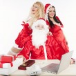 Santa Claus with two sexy helpers in his office — Stock Photo