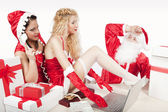 Santa Claus with two sexy helpers in his office — ストック写真