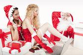 Santa claus mit zwei sexy helfer in seinem büro — Stockfoto