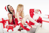 Santa Claus with two sexy helpers in his office — Stok fotoğraf