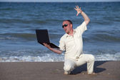 Angry man punching laptop at the beach — Stock Photo