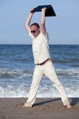 Angry man throwing his laptop at the beach — Stock Photo