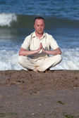 Young businessman doing yoga on a beach — Stock Photo