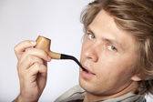 Attractive young man smoking pipe — Stock Photo