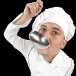 Young chef tasting soup from a ladle — Stock Photo