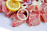 Sliced pork with onion and lemon — Stock Photo