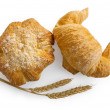 Croissant and bread roll with stems of wheat — Stock Photo