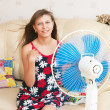 The girl sits in front of the fan — Стоковое фото