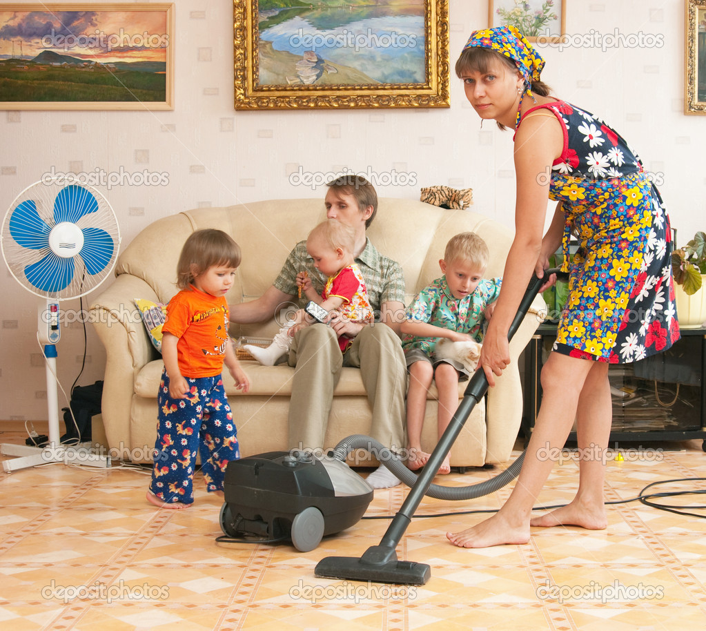 The tired woman vacuums and the family has a rest on a sofa — Stock Photo #4411869