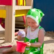 The girl playing to a sandbox — Stockfoto