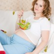 Pregnant woman in bed eating — Stock Photo #4926061