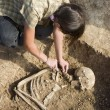 Archaeologist excavatin skeleton — Stock Photo