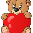 Cute teddy bear holding heart - Stock Vector