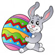 Cartoon bunny holding Easter egg - Stock Vector