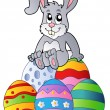 Bunny on pile of Easter eggs — Stock Vector