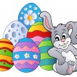 Bunny resting beside Easter eggs - Stock Vector