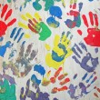 Rainbow color handprint on concrete white wall, friendship. — Stock Photo