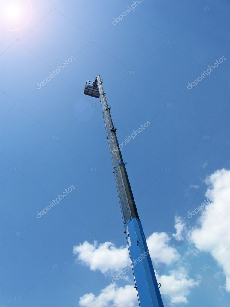 High long industrial crane arm with cradle on blue sky with white clouds, bright sun. heaven way road concept  Stock Photo #4143849