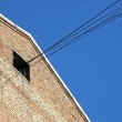 Red brick wall, cables from loft, connections on blue sky. — Stock Photo #4991020
