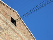 Red brick wall, cables from loft, connections on blue sky. — Stock Photo