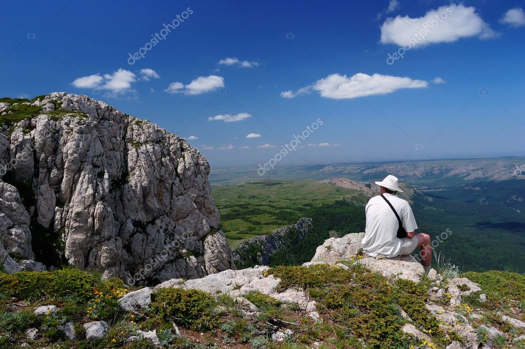 Summer landscape with the man sitting on a rock and the cloudy sky. — Stock Photo #4591441