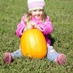 Little gardener girl with pumpkin at green grass — Stock Photo #3941059