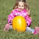 Little gardener girl with pumpkin at green grass — Stock Photo #3941060