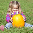 Little gardener girl with pumpkin at green grass — Stock Photo #3941070