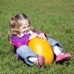 Little gardener girl with pumpkin at green grass — Stock Photo #3941078