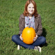 Young women sitting at green grass and keeping pumpkin. — Stock Photo