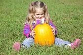 Little gardener girl with pumpkin at green grass — Stock Photo