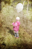 Little girl with balloon at park. Photo in old retro colour imag — Stock Photo