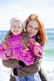 Deux soeurs 4 et 21 ans à la plage en journée ensoleillée d'automne. — Photo