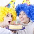 Foto Stock: Two girlfriends with cake and wig celebrate 21th birthday