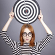 Red-haired girl with dartboard. — Stock Photo
