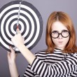 Angry red-haired girl with dartboard. - Foto Stock