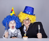 Mother and child in funny wigs and cake at birthday. Studio shot — Stock Photo